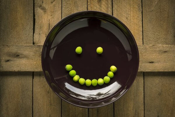 A picture of a smiley face made of peas, can emojis encourage children to make healthy eating choices, Be Curious