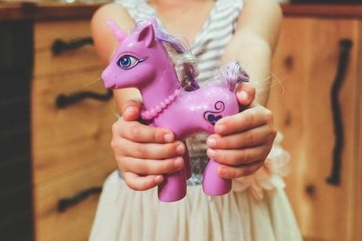 Picture of a girl holding a pink unicorn, are gender specific toys causing stereotypes in education and the work place?, Be Curious