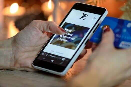 A woman purchasing online using her mobile phone, why are UK mums leading the way in online purchasing, Be Curious