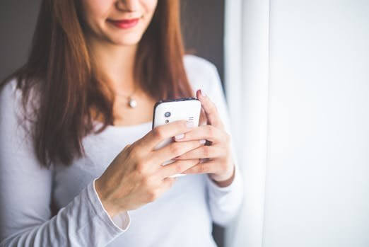 Image of a mum using a mobile phone, why mobile is the best way to reach Mum, Be Curious